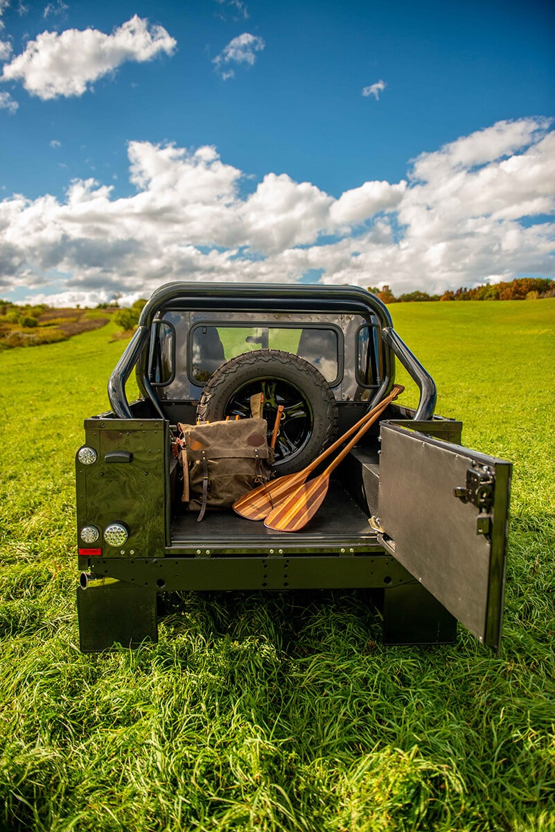 Land Rover Defender D110 Double Cab Bowler Bulldog: Exterior Truck back with open gate and paddles and pack